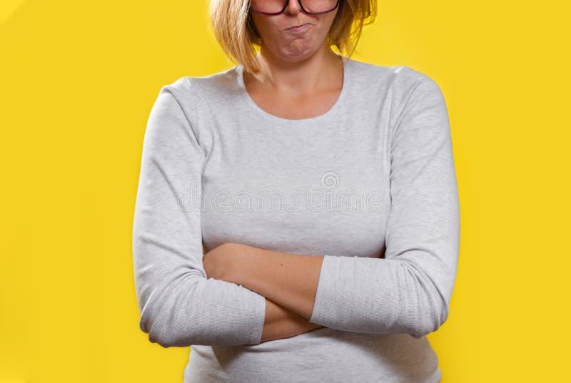 Emotion och psykologi Kvinnan, en blond med glasögon, korsade hennes armar och snörpte hennes läppar med ett missnöjt ansikte Stä fotografering för bildbyråer