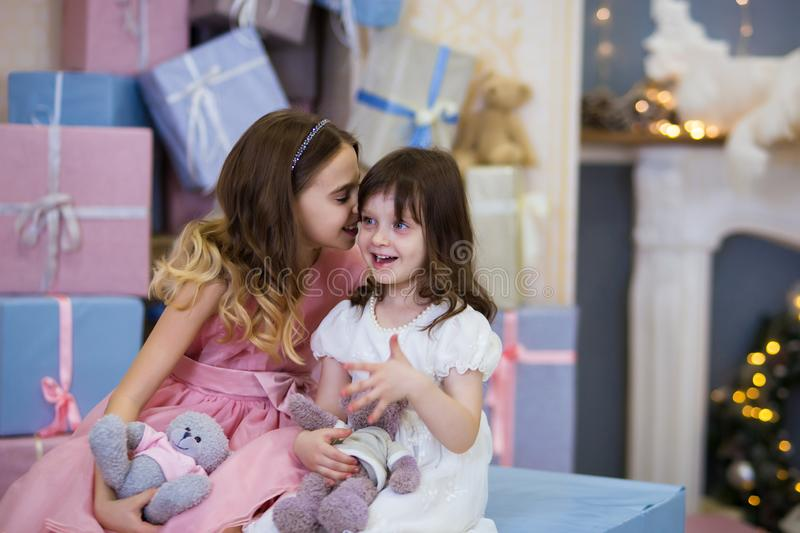 Emotion of surprise baby. Beautiful little girl with blond hair in a pink and white dress tells a secret in her ear. in the royalty free stock image