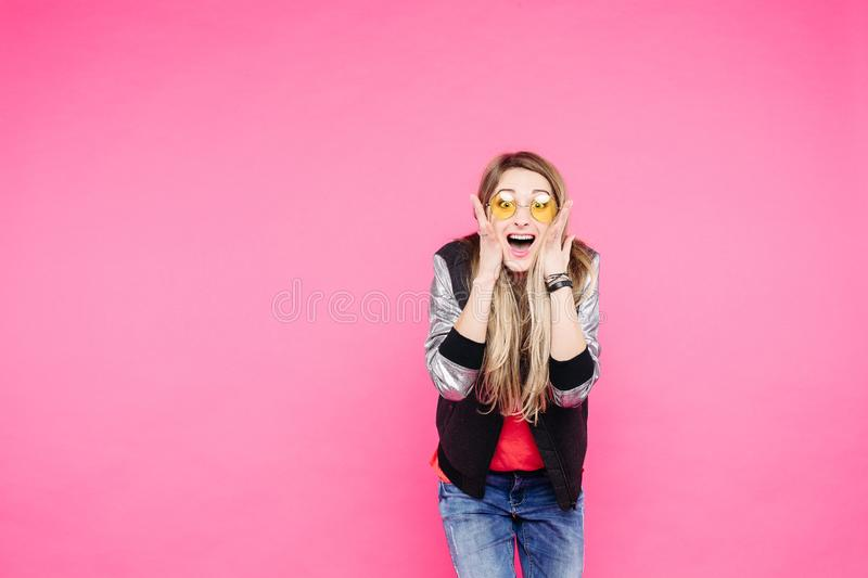 Emotion teen girl in yellow sunglaases against pink studio background. royalty free stock photo