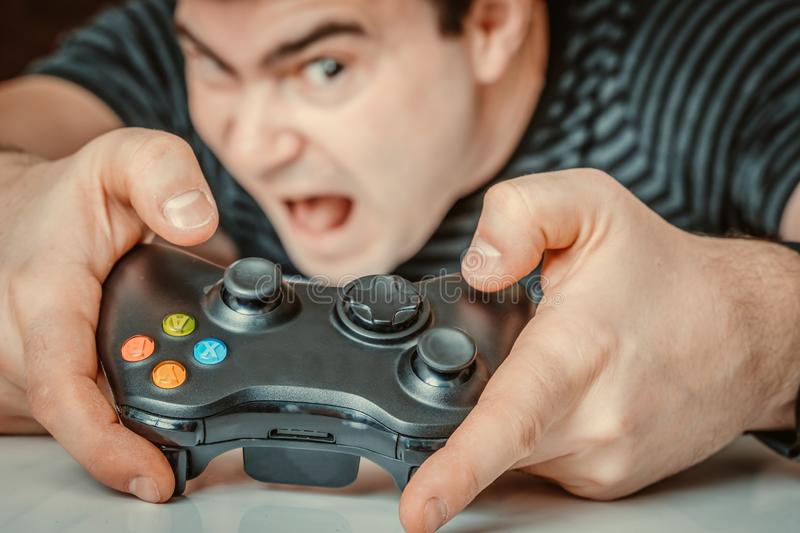 Emotional addicted man playing video games royalty free stock image