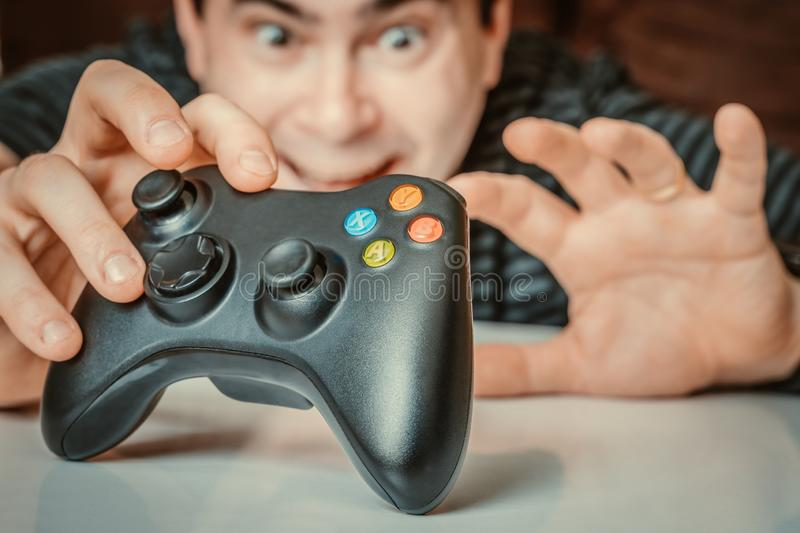 Emotional addicted man playing video games stock photography