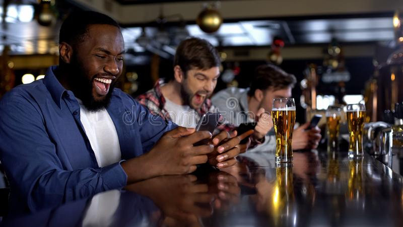 Emotional african-american male celebrating winning bet on match, bookmaker app. Stock photo royalty free stock image