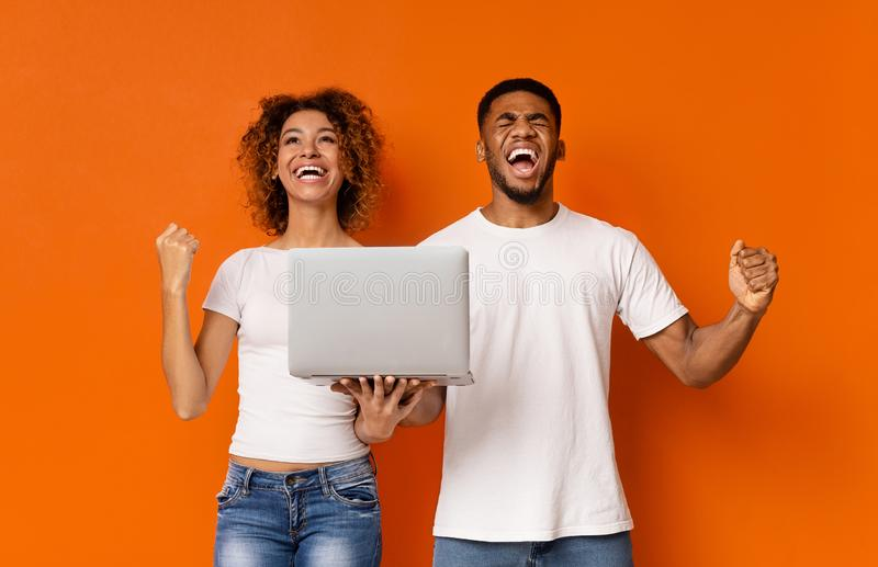 Emotional african couple with laptop enjoying win stock photos