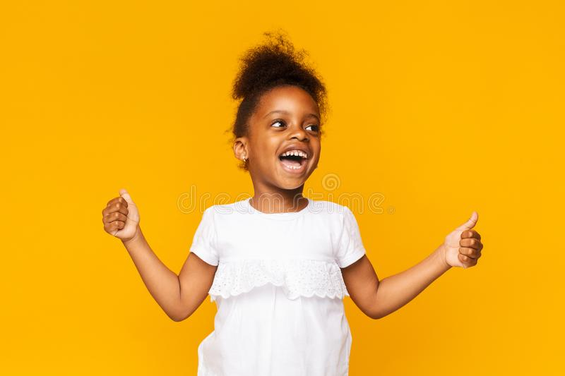 Emotional african little girl showing thumbs up and shouting stock photos