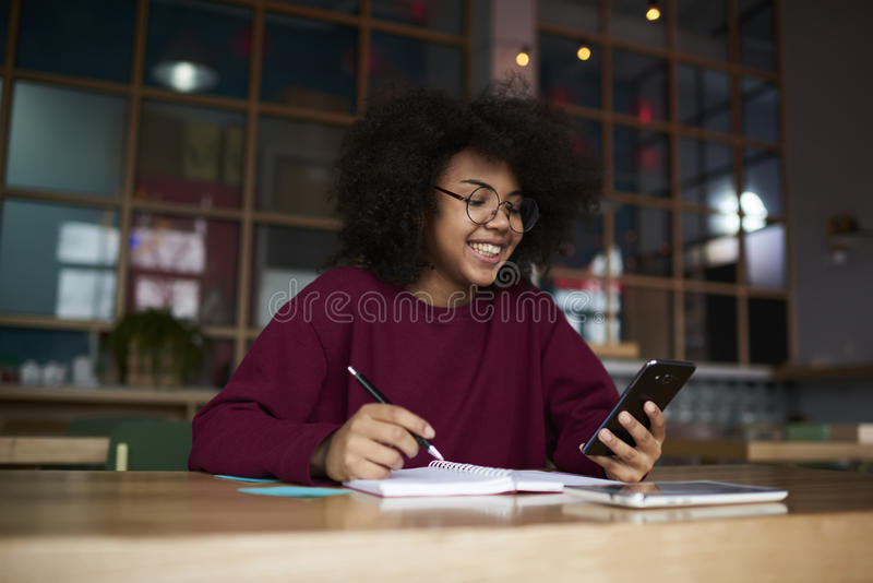 Emotional Afro-american business school student followers via modern smartphone and free wireless connection stock photography