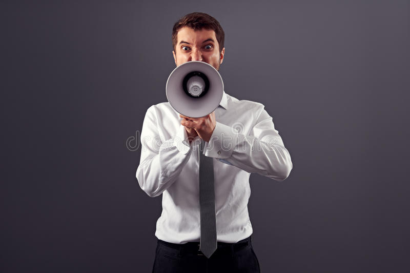 Emotional angry man shouting with megaphone