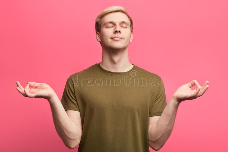 Emotional attractive man feels relaxed, mediates royalty free stock photography