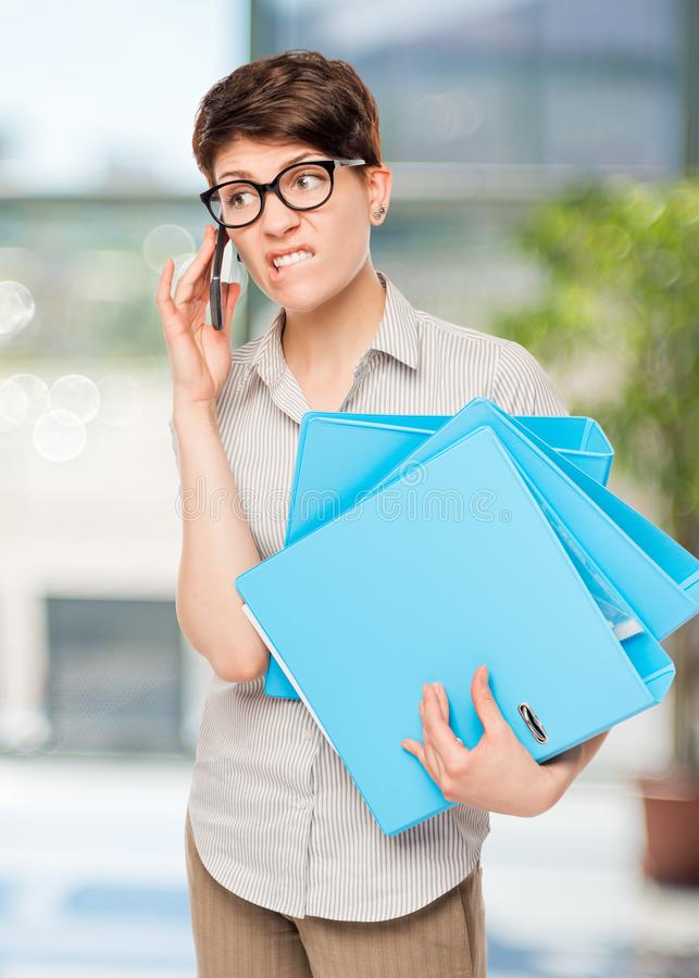 emotional baffled girl talking on the phone with the boss royalty free stock images