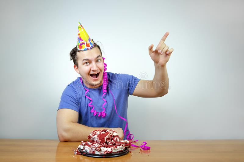 Emotional beautiful caucasian man with birthday party cone hat on head and crumple cake raises your index finger up, smiling happi stock photo