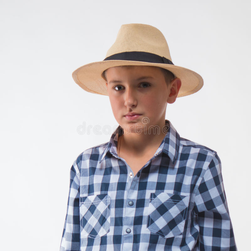 Emotional blond boy checkered shirt and straw hat. On a white background stock image