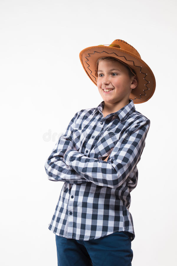 Emotional blond boy in a plaid shirt, sunglasses and a cowboy hat. On a white background royalty free stock images
