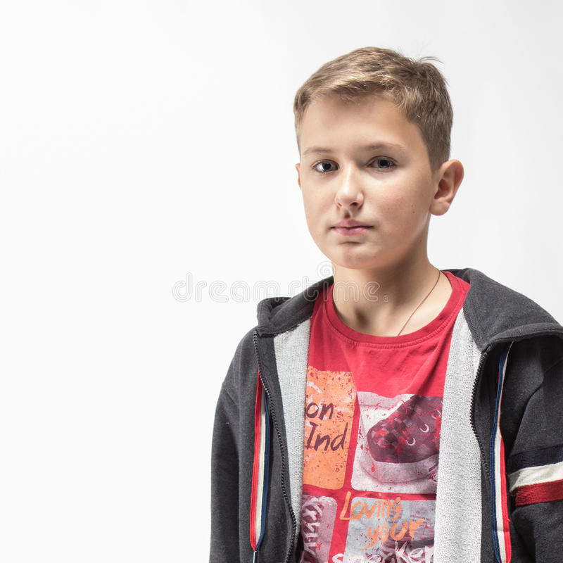Emotional blond boy in the red shirt. Over a white background royalty free stock image