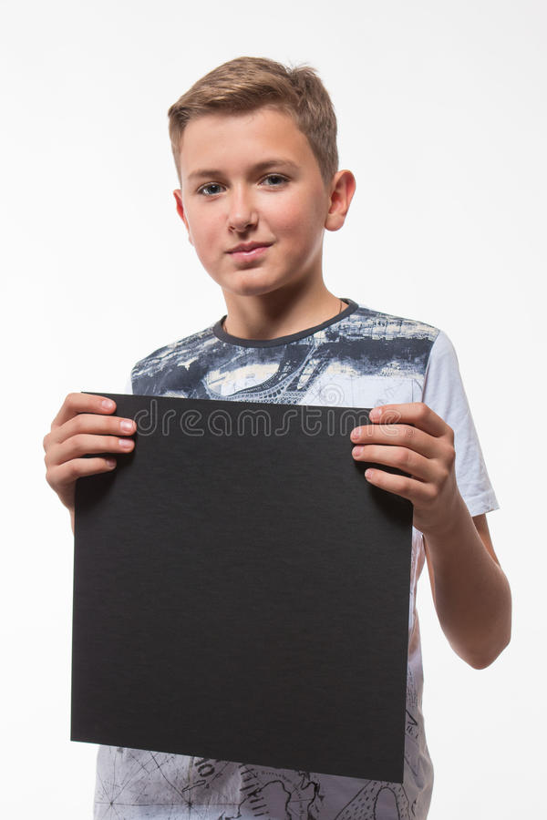 Emotional blond boy in a white shirt with a gray sheet of paper for notes. On a white background royalty free stock photography