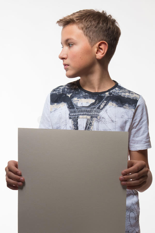 Emotional blond boy in a white shirt with a gray sheet of paper for notes. On a white background royalty free stock image
