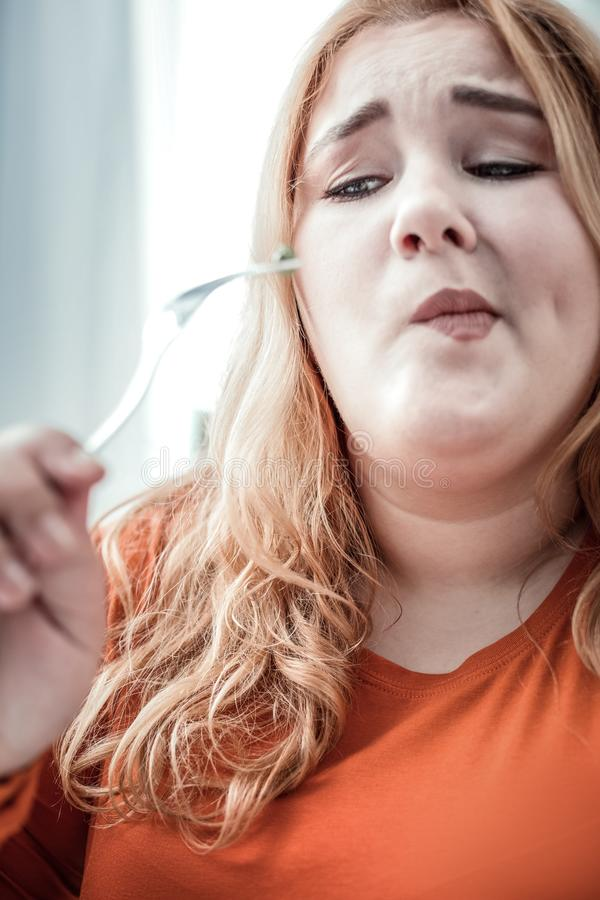 Emotional blonde female person making her face. Hate it. Plump girl wrinkling forehead while looking at fork royalty free stock images