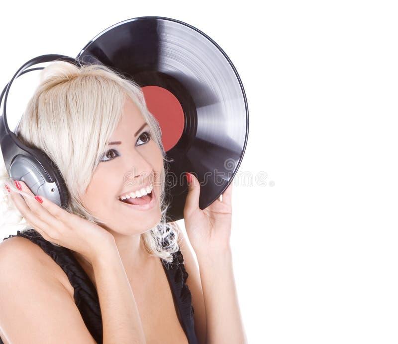 Emotional blonde in headphones with vinyl record stock image