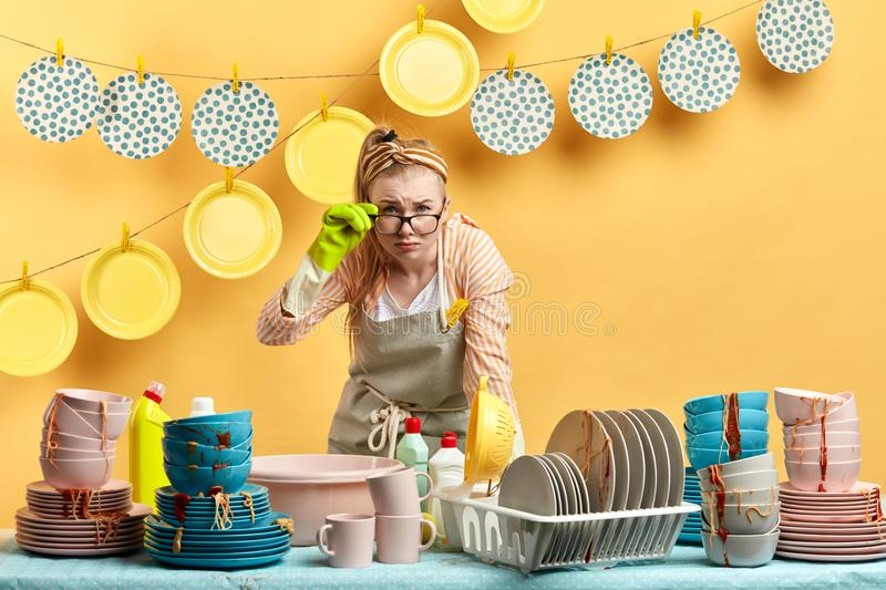 Emotional blonde housewife with sceptical expression looking at the camera stock images