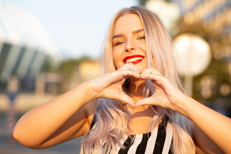 Emotional blonde model with red lips making heart sign with her fingers at the street. Space for text stock images