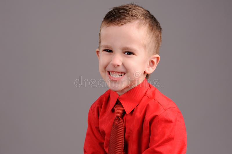 Emotional boy. Portrait of emotionally kid. Emotional boy on the grey background, adorable, childhood, defiance, fun, gesture, look, looking, model, male, posing royalty free stock photography