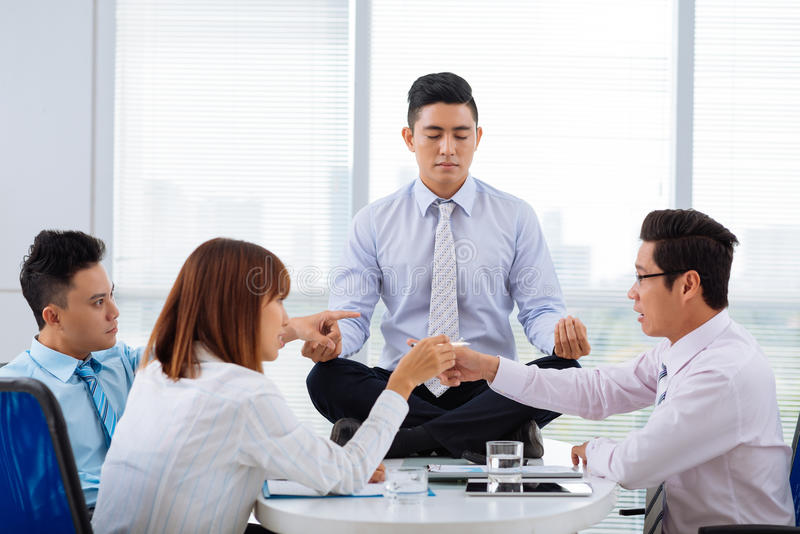 Emotional business meeting. Asian business people arguing while their colleague sitting on the table in lotus position royalty free stock images