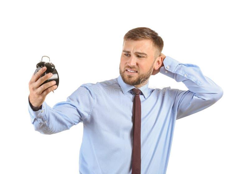 Emotional businessman with alarm clock on white background stock photo