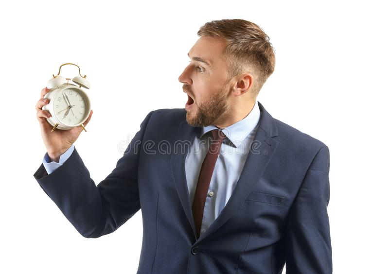 Emotional businessman with alarm clock on white background royalty free stock photos
