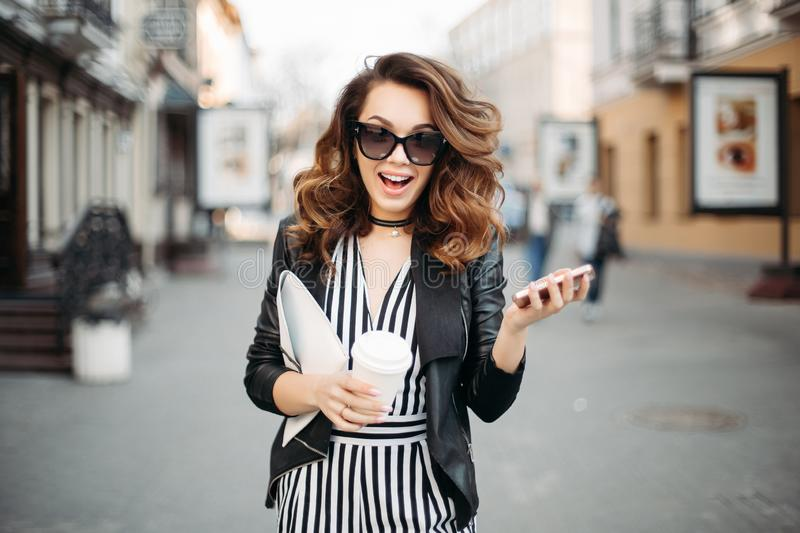 Emotional busy brunette at street talking on call phone. Emotional busy brunette woman at street, talking and using call phone, drinking coffee. Beautiful royalty free stock photos