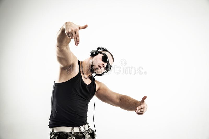 Emotional and charismatic DJ - rapper in headphones takes the ra. DJ - rapper in headphones takes the rap and break dancing dance on a light background.the photo royalty free stock image
