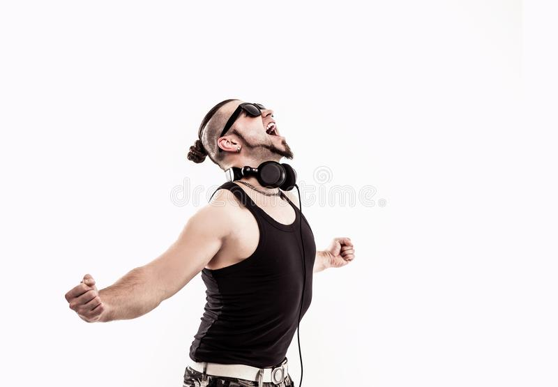 Emotional and charismatic DJ - rapper in headphones takes the ra. DJ - rapper in headphones takes the rap and break dancing dance on a light background.the photo royalty free stock images