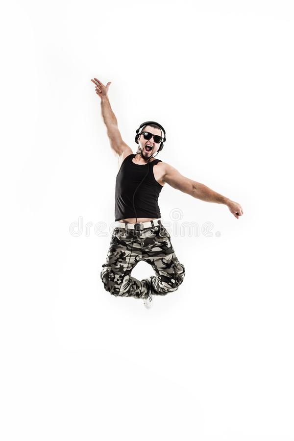 Emotional and charismatic DJ - rapper in headphones takes the ra. DJ - rapper in headphones takes the rap and break dancing dance on a light background.the photo stock photo