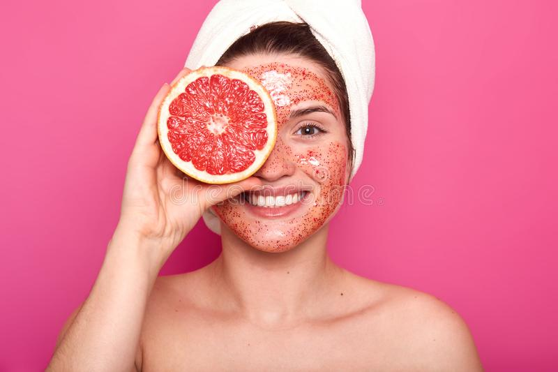 Emotional charismatic young woman with a beautiful smile on her face spends time doing beauty procedures, makes her skin fresh and royalty free stock images