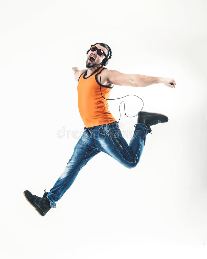 Emotional and charming guy - rapper in headphones takes the dance. Charming guy - rapper in headphones takes the dance break.photo on a white background and has royalty free stock images