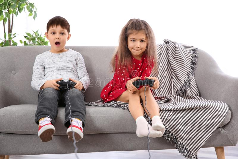 Emotional children playing video game on sofa stock image