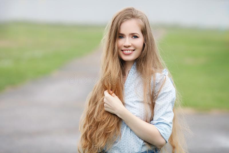 Emotional close up portrait of a adult pretty blonde woman with gorgeous extra long hair posing outdoors against blurred park back stock photos