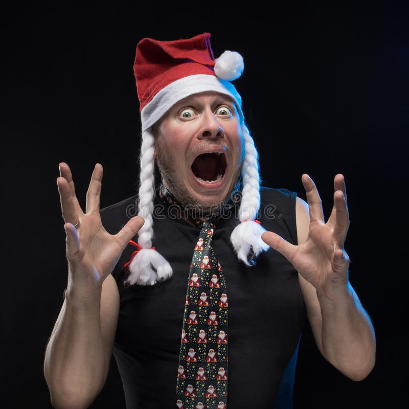 Emotional Comic actor man in cap with braids gesticulates, in anticipation of Christmas and New Year. Emotional Comic actor man in cap with braids gesticulates royalty free stock photography