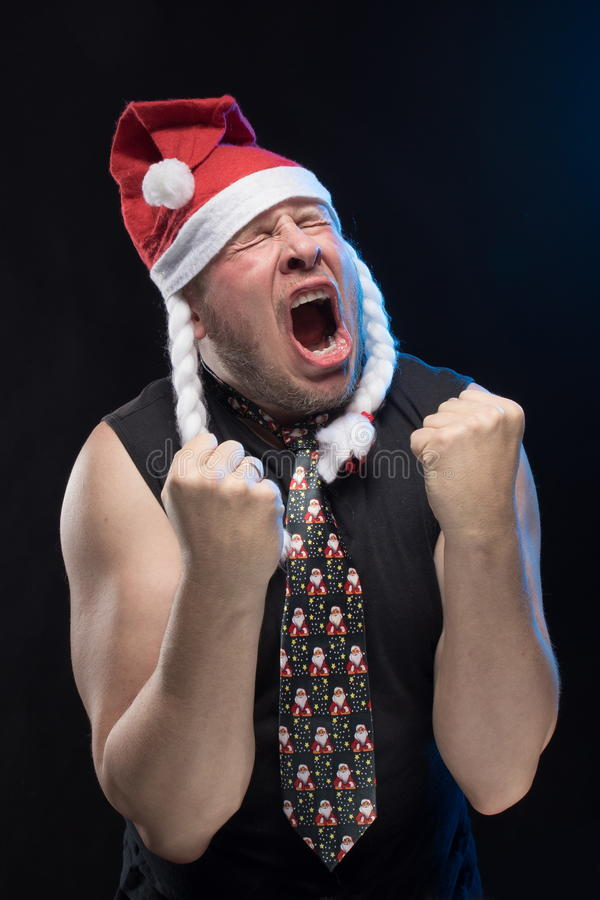 Emotional Comic actor man in cap with braids gesticulates, in anticipation of Christmas and New Year. Emotional Comic actor man in cap with braids gesticulates royalty free stock photo