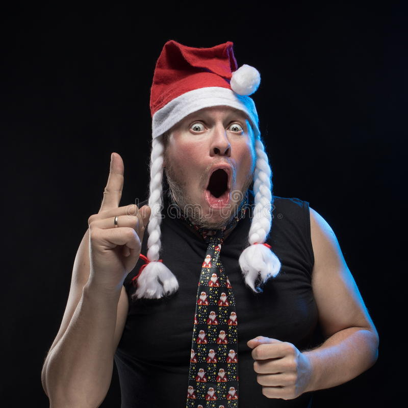 Emotional Comic actor man in cap with braids gesticulates, in anticipation of Christmas and New Year. Emotional Comic actor man in cap with braids gesticulates stock photo