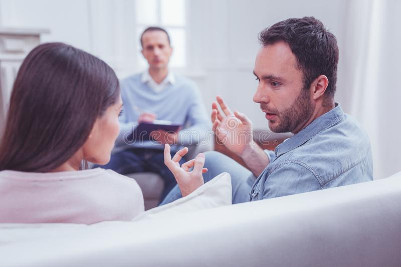 Emotional couple discussing relationships during psychological therapy royalty free stock photo