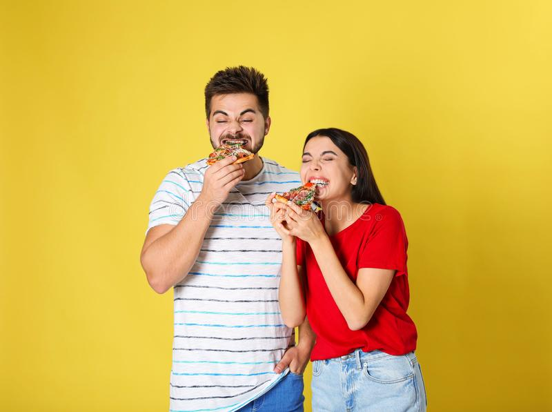 Emotional couple eating pizza on background royalty free stock images
