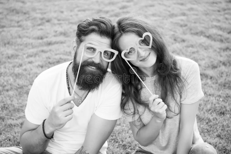 Emotional couple radiating happiness. Love story. Couple relaxing green lawn. Man bearded hipster and pretty woman in royalty free stock images