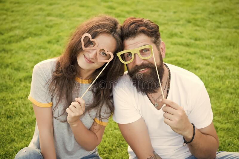 Emotional couple radiating happiness. Love story. Couple relaxing green lawn. Man bearded hipster and pretty woman in royalty free stock photos