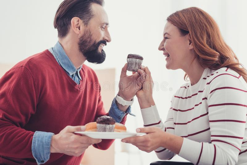 Emotional couple smiling while eating tasty cakes together. Fresh cakes. Positive romantic young couple feeling happy while sitting together and eating delicious royalty free stock image