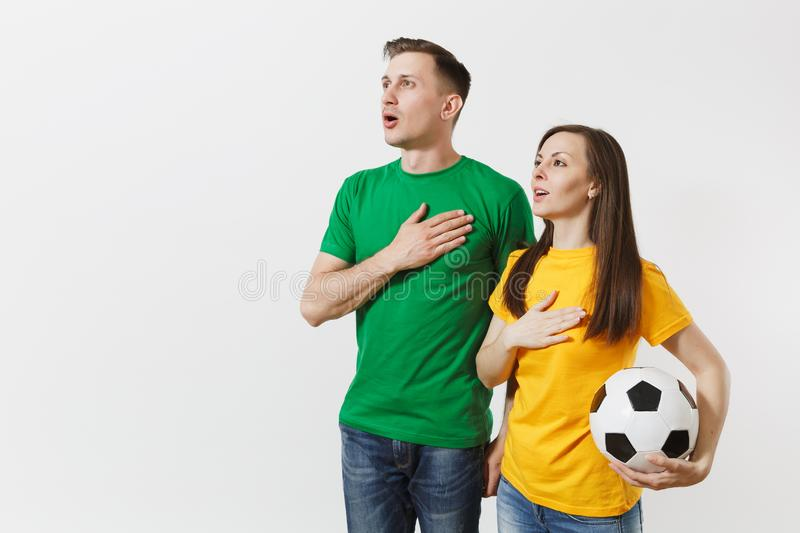Emotional couple, woman man, football fans in yellow green t-shirt cheer up support team with soccer ball singing royalty free stock photo