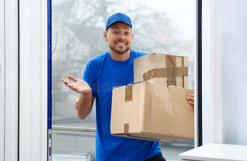 Emotional courier with damaged cardboard boxes in doorway. Poor quality delivery service stock photo