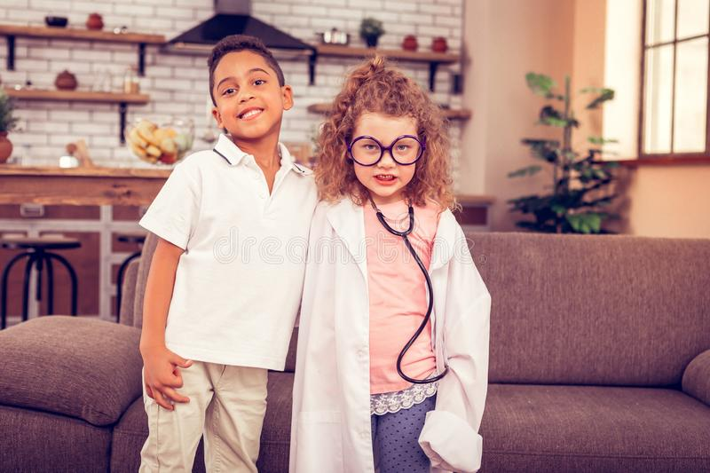 Emotional curly-haired girl staring straight at camera. Love her. Kind international boy expressing positivity while embracing his friend stock images