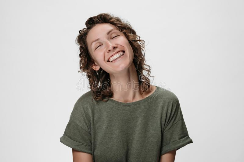 Emotional curly woman smiling widely, closing her eyes royalty free stock images