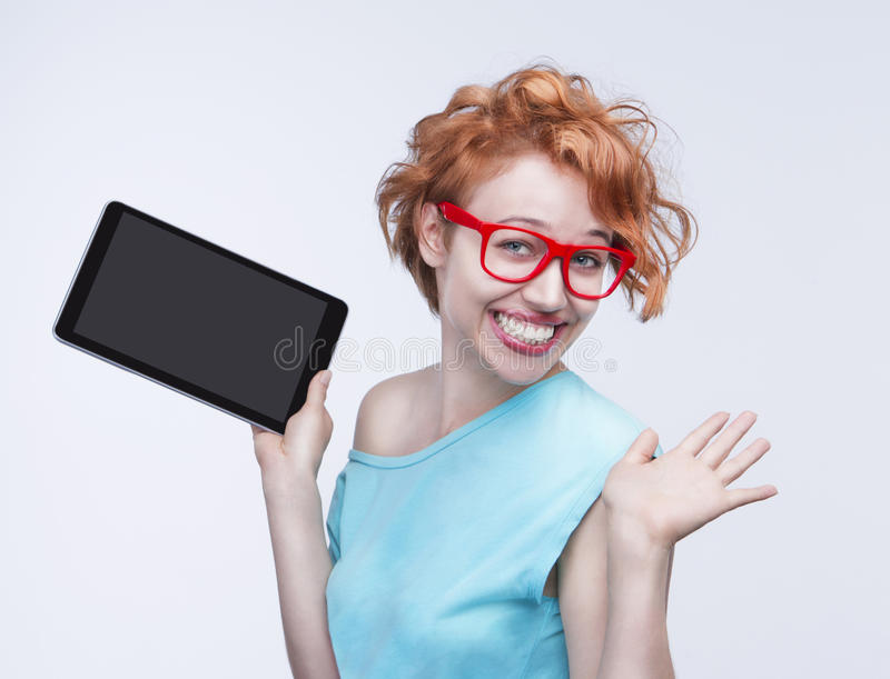 Emotional cute red-haired girl holding tablet computer, opening hands. Broad pretty attractive friendly smile with teeth. Empty space on the tablet pc, you can royalty free stock images