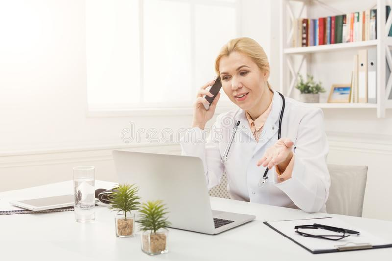 Emotional doctor talking on the phone with her patient stock image