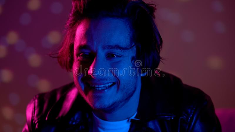 Emotional drunk man laughing and crying at party, confused and lost in life. Stock photo stock image