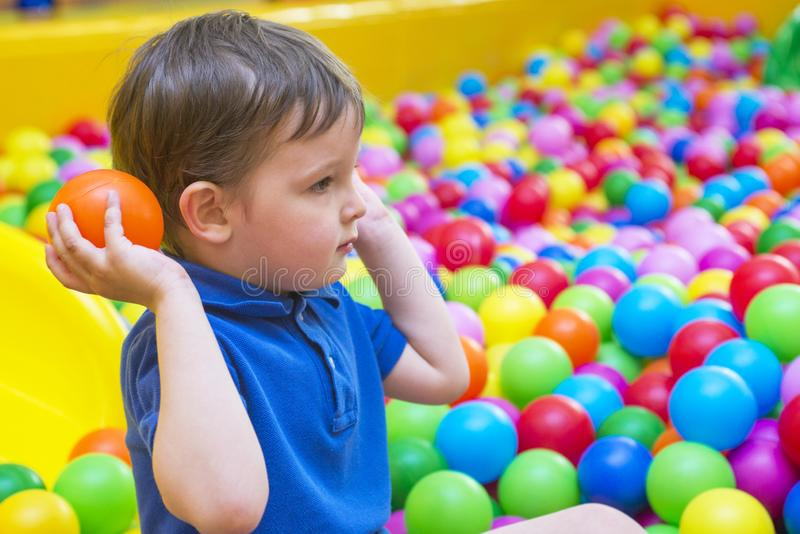An emotional face of smiling baby playing in the balls pool. Happy kid playing with colored balls. Child playing with colorful bal stock images